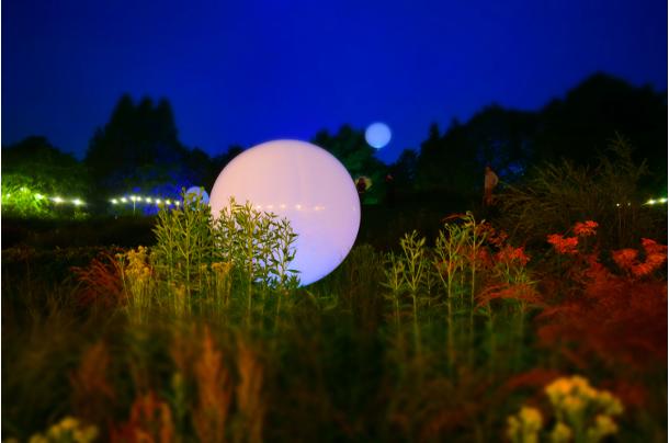 weather ballon lit inside in garden at night
