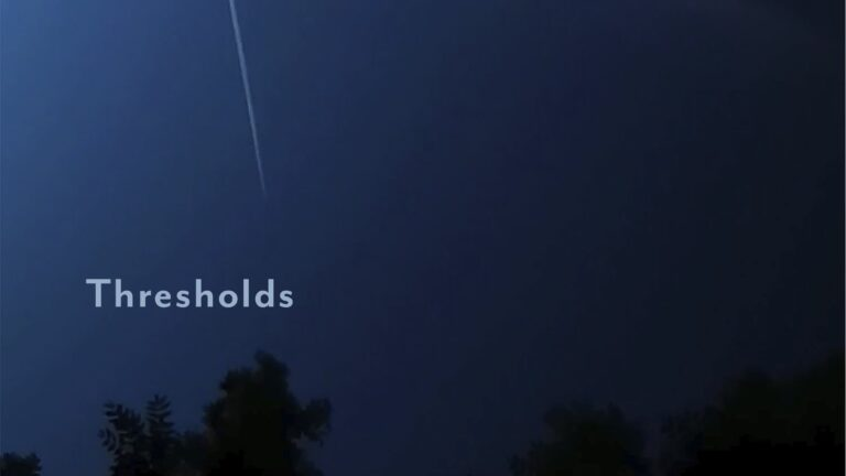 A blue night sky with a contrail