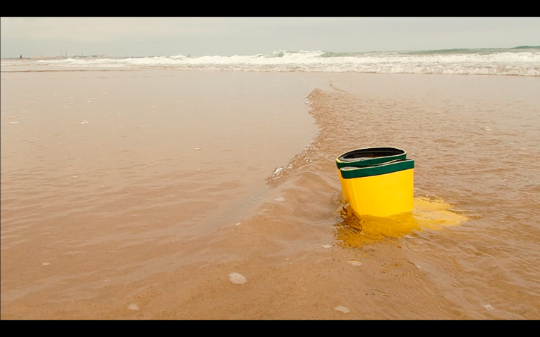Yellow wellingtons and lapping water at low incoming tide