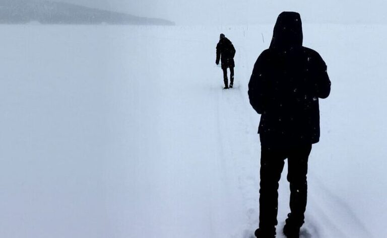 two figures in the snow walking away